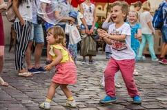 LVIV UKRAINA - AUGUSTI 2016: Unga barn som fångar såpbubblor i staden, spelar, glat och utstrålar positiva sinnesrörelser, mummel arkivbild