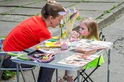 LVIV UKRAINA, CZERWIEC, - 2016: Kobieta mistrzowski artysta maluje słodkiego powabnego dziewczyny dziecka na twarzy wąsy i kot ma Fotografia Royalty Free