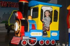 LVIV UKRAINA - JANUARI 2018: Den lilla charmiga flickan barnet går för en ritt i ett nöjesfält på karusellen och spelar videoen Arkivbilder