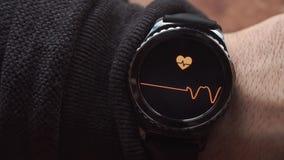 Lviv Ukraina - Januari 2017: Smartwatch som visar hjärtahastigheten till användaren lager videofilmer