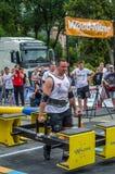 LVIV UKRAINA - JULI 2016: Den starka idrottsman nenkroppsbyggarestrongmanen bär laget för världen för heavy metaldesignkonkurrens Arkivfoton
