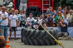 LVIV UKRAINA - JULI 2016: Den starka idrottsman nenstrongmanen som drar ett replastbilsammanträde med en partner, är inte enorma  Arkivbilder