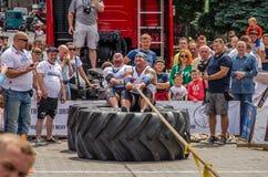 LVIV UKRAINA - JULI 2016: Den starka idrottsman nenstrongmanen som drar ett replastbilsammanträde med en partner, är inte enorma  Royaltyfria Foton