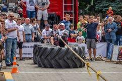 LVIV UKRAINA - JULI 2016: Den starka idrottsman nenstrongmanen som drar ett replastbilsammanträde med en partner, är inte enorma  Arkivfoto