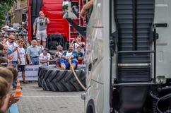 LVIV UKRAINA - JULI 2016: Den starka idrottsman nenstrongmanen som drar ett replastbilsammanträde med en partner, är inte enorma  Royaltyfria Bilder