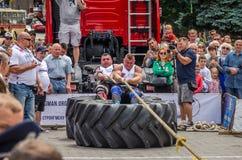 LVIV UKRAINA - JULI 2016: Den starka idrottsman nenstrongmanen som drar ett replastbilsammanträde med en partner, är inte enorma  Royaltyfri Foto