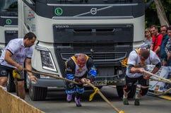 LVIV UKRAINA - JULI 2016: Stark kroppsbyggarestrongman för idrottsman nen som två framme drar med den enorma lastbilen för rep tv Arkivfoto