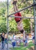 Lviv Ukraina - Juli 2015: Yarych gataFest 2015 Idrottsman nen som gör övningar på horisontalstången Arkivfoton