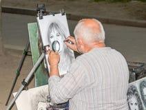 Lviv Ukraina - Juni 2015: Målaren målar en stående av gataflickan med blyertspennan och papper för foto arkivfoton