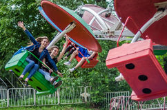 LVIV UKRAINA - JUNI 2016: Två härliga ung flickatonår rider på karusellen i ett nöjesfält, med lyckliga glade sinnesrörelser Royaltyfri Fotografi