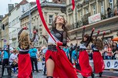 LVIV UKRAINA - JUNI 2016: Unga charma sexiga flickor utför en dans med henne på gatan framme av åhörarna i det rött, w Royaltyfri Fotografi