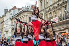 LVIV UKRAINA - JUNI 2016: Unga charma sexiga flickor utför en dans med henne på gatan framme av åhörarna i det rött, w Royaltyfri Bild