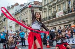 LVIV UKRAINA - JUNI 2016: Unga charma sexiga flickor utför en dans med henne på gatan framme av åhörarna i det rött, w Royaltyfria Bilder