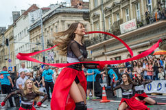 LVIV UKRAINA - JUNI 2016: Unga charma sexiga flickor utför en dans med henne på gatan framme av åhörarna i det rött, w Royaltyfri Foto