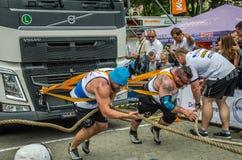 LVIV UKRAINA, LIPIEC, - 2016: Dwa atlety bodybuilder siłacza silny ciągnięcie z arkan dwa ogromną ciężarówką przed entuzjastyczny Fotografia Royalty Free