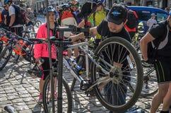 LVIV UKRAINA - MAJ 2018: Cyklisten reparerar hans cykel, genom att pumpa ett punkterat hjul arkivbilder
