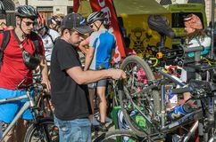 LVIV UKRAINA - MAJ 2018: Cyklisten reparerar hans cykel, genom att pumpa ett punkterat hjul royaltyfri fotografi