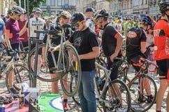 LVIV UKRAINA - MAJ 2018: Cyklisten reparerar hans cykel, genom att pumpa ett punkterat hjul arkivbild
