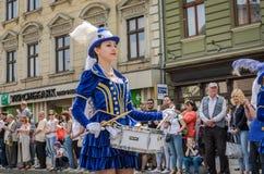 LVIV UKRAINA - MAJ 2018: Gulliga unga flickor med valsar i blåa karnevaldräkter och hattar med fjädrar under ståta i cen Royaltyfri Bild