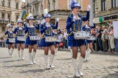 LVIV UKRAINA - MAJ 2018: Gulliga unga flickor med valsar i blåa karnevaldräkter och hattar med fjädrar under ståta i cen Arkivfoto