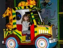 LVIV UKRAINA - NOVEMBER 2017: Den lilla charmiga flickan barnet går för en ritt i ett nöjesfält på karusellen och spelar videoen Royaltyfri Fotografi