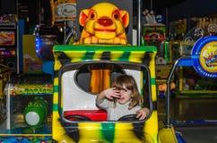 LVIV UKRAINA - NOVEMBER 2017: Den lilla charmiga flickan barnet går för en ritt i ett nöjesfält på karusellen och spelar videoen Royaltyfri Foto
