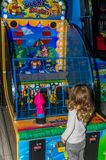 LVIV UKRAINA - NOVEMBER 2017: Den lilla charmiga flickan barnet går för en ritt i ett nöjesfält på karusellen och spelar videoen Royaltyfria Foton