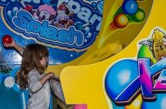 LVIV UKRAINA - NOVEMBER 2017: Den lilla charmiga flickan barnet går för en ritt i ett nöjesfält på karusellen och spelar videoen Fotografering för Bildbyråer