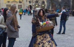 LVIV UKRAINA - November 15: Flickan i en härlig dräkt säljer godisen i den Lviv marknadsfyrkanten, November 15, 2015 i Lviv, Ukra Arkivfoton
