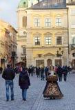 LVIV UKRAINA - November 15: Flickan i en härlig dräkt säljer godisen i den Lviv marknadsfyrkanten, November 15, 2015 i Lviv, Ukra Arkivbild