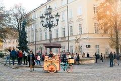 LVIV UKRAINA, OCT, - 31, 2018: Turyści odpoczywa blisko fontanny Adonis Rowerów cukierki Lviv zdjęcie stock