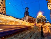 LVIV UKRAINA - SEPTEMBER 12, 2016: Lviv stad och Lviv gammal stad med folk Solnedgångljus och Lviv stad Hall With Moving Tram Blå Royaltyfri Bild