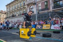 LVIV UKRAINA, SIERPIEŃ, - 2017: Silna atleta bodybuilder niesie ciężkie żelazne walizki, wewnątrz ćwiczy średniorolnego ` s space Zdjęcie Stock