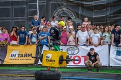 LVIV UKRAINA, SIERPIEŃ, - 2017: Silna atleta bodybuilder niesie ciężkie żelazne walizki, wewnątrz ćwiczy średniorolnego ` s space Obrazy Royalty Free
