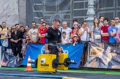 LVIV UKRAINA, SIERPIEŃ, - 2017: Silna atleta bodybuilder niesie ciężkie żelazne walizki, wewnątrz ćwiczy średniorolnego ` s space Obraz Stock