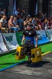 LVIV UKRAINA, SIERPIEŃ, - 2017: Silna atleta bodybuilder niesie ciężkie żelazne walizki, wewnątrz ćwiczy średniorolnego ` s space Fotografia Stock