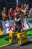 LVIV UKRAINA, SIERPIEŃ, - 2017: Silna atleta bodybuilder niesie ciężkie żelazne walizki, wewnątrz ćwiczy średniorolnego ` s space Zdjęcia Royalty Free