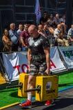 LVIV UKRAINA, SIERPIEŃ, - 2017: Silna atleta bodybuilder niesie ciężkie żelazne walizki, wewnątrz ćwiczy średniorolnego ` s space Obrazy Stock