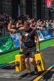 LVIV UKRAINA, SIERPIEŃ, - 2017: Silna atleta bodybuilder niesie ciężkie żelazne walizki, wewnątrz ćwiczy średniorolnego ` s space Zdjęcia Stock