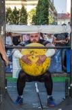 LVIV UKRAINA, SIERPIEŃ, - 2017: Silna atleta bodybuilder podnosi ogromną ciężką kamienną żółtą piłkę przy siłacz grami Zdjęcie Royalty Free