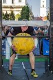 LVIV UKRAINA, SIERPIEŃ, - 2017: Silna atleta bodybuilder podnosi ogromną ciężką kamienną żółtą piłkę przy siłacz grami Obraz Royalty Free