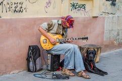 LVIV UKRAINA, SIERPIEŃ, - 2016: Uliczny muzyk bawić się rockowych uderzenia gitara elektryczna, siedzi z wielkim czarnym psem, bl Obraz Royalty Free