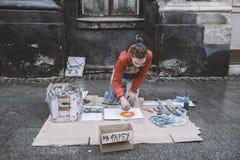 Lviv Ukraina, Styczeń, - 21, 2018: Kiści farby przedstawienie dla widowni po środku ulicy, młody piękny obsiadanie na kolanach Obrazy Stock