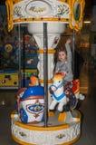 LVIV UKRAINA, STYCZEŃ, - 2018: Mała powabna dziewczyna dziecko iść dla przejażdżki w parku rozrywki na carousel wideo sztukach i fotografia stock