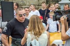 LVIV, UKRAINE - AOÛT 2015 : L'athlète fort du ` s d'homme fort est pris par un journaliste de TV Photo stock