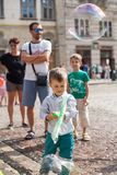 Lviv, Ukraine - August 12, 2018: Happy little boy playing with soap bubbles on the main square of Lviv royalty free stock photos