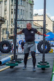 LVIV, UKRAINE - AUGUST 2017: Strong athlete bears a heavy huge rocker on the heroic games at Strongmen game Stock Photography