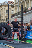 LVIV, UKRAINE - AUGUST 2017: Strong athlete bears a heavy huge rocker on the heroic games at Strongmen game Royalty Free Stock Photos