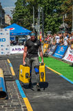 LVIV, UKRAINE - AUGUST 2017: A strong athlete a bodybuilder carries heavy iron suitcases, in exercise a farmer`s walk, on the stro Royalty Free Stock Photo