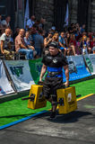 LVIV, UKRAINE - AUGUST 2017: A strong athlete a bodybuilder carries heavy iron suitcases, in exercise a farmer`s walk, on the stro Stock Photography